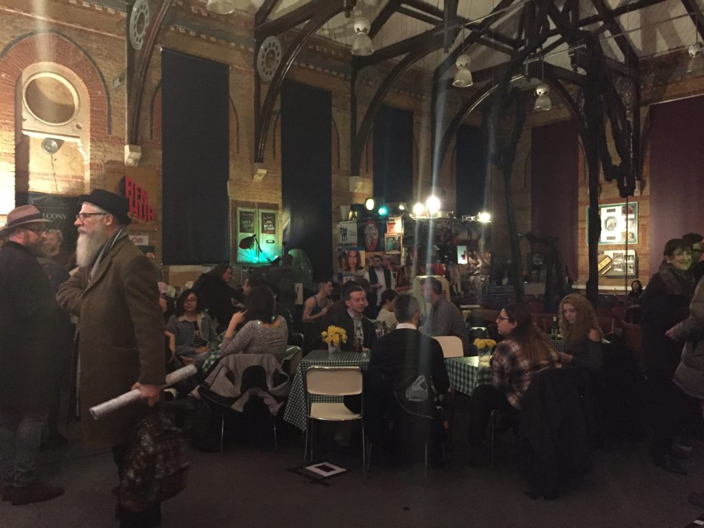 Photograph of attendees sat around small tables at the Cinema Museum. The tables are adorned with flowers and chequered green and white table cloth. To the left of the image is the bar, where two men with hats and beards stand, facing opposite directions.